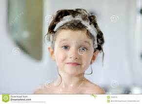 Nice toddler girl in bath with shampoo stock photography