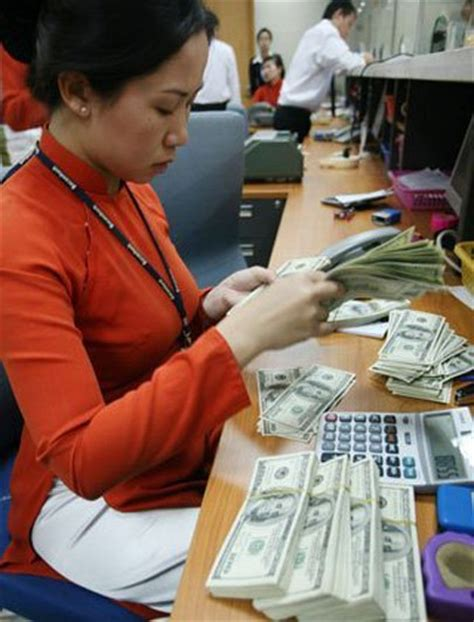 a bank teller counts dollar banknotes the remittance amount to hcmc has increased by 15 this
