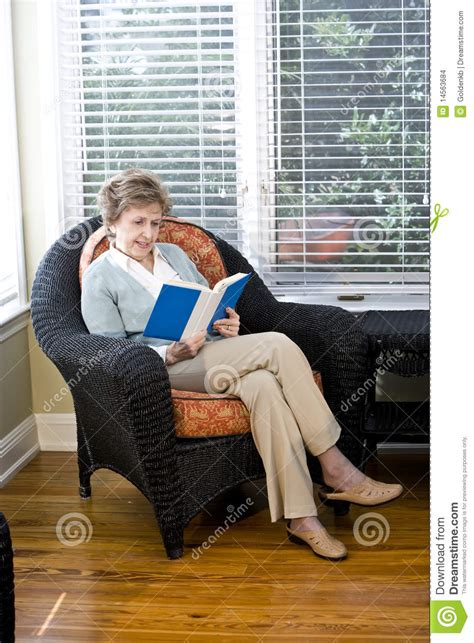 reading ls for living room senior woman sitting on living room chair reading stock