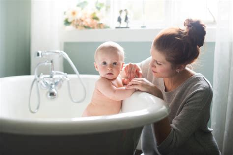 Giving In Bathroom giving baby bath stock photo getty images