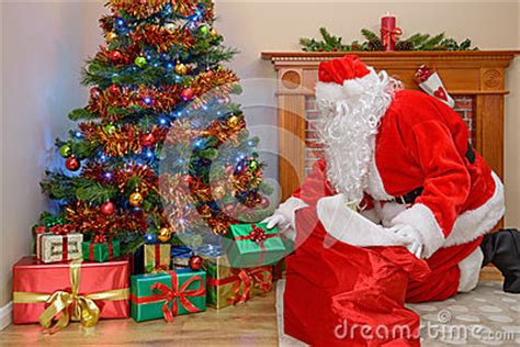 father christmas putting gifts   tree stock photo