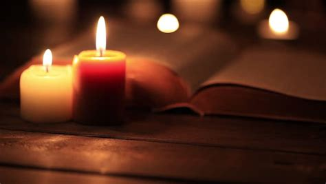 open bible and reading glasses in candle light stock