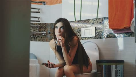 how to smoke a cigarette in the bathroom girl sitting on toilet with smartphone smoking electronic