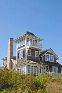 Grey shingle style beach house with lookout tower and white framed