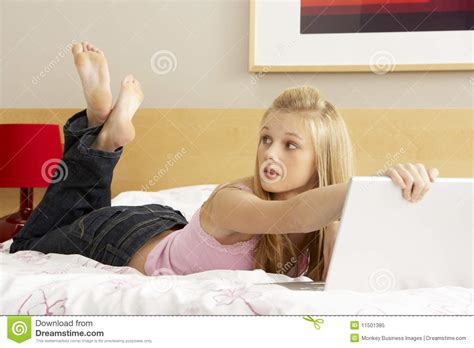 girl on bed guilty teenage girl using laptop in bedroom stock image