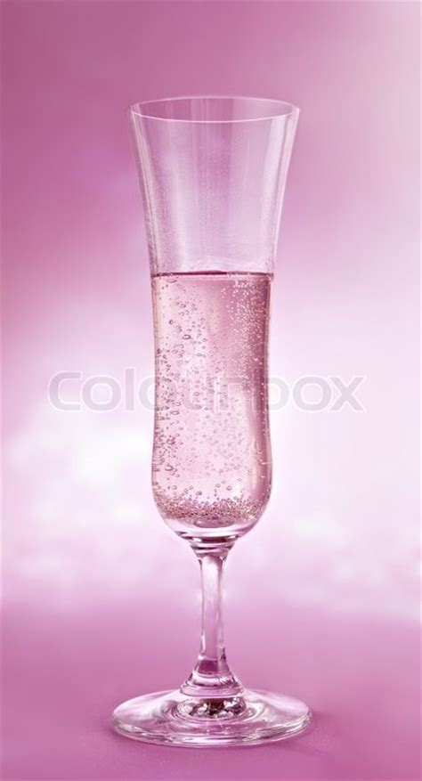 A glass of champagne on pink background   Stock Photo
