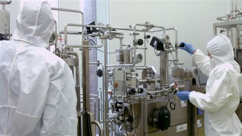 format factory high quality scientists in protective suits working on vat in high