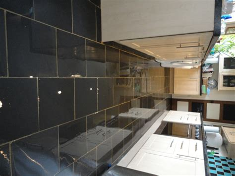 dull and stained semi riven black slate floor tiles in