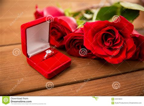 close   diamond engagement ring  red roses stock