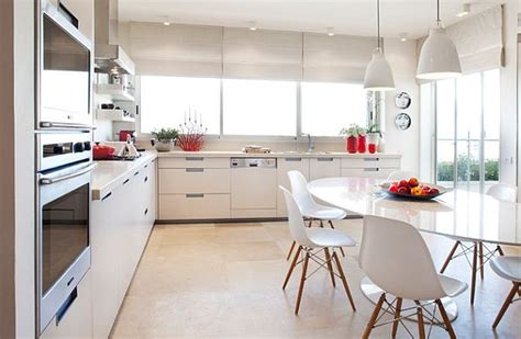 white kitchen with oval shaped table and eames chairs