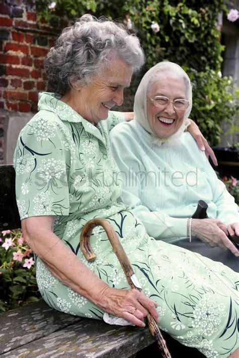 old woman fun two old women having fun sitting on the bench talking