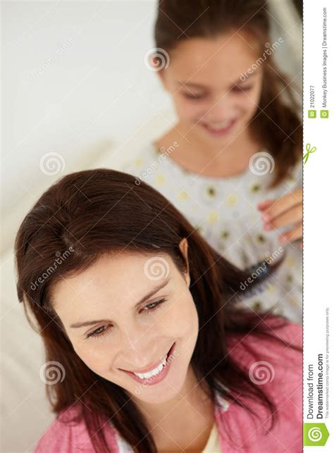 young girl brushing mothers hair stock image image