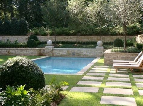 backyard love pool surrounded by grass with stone pavers backyard