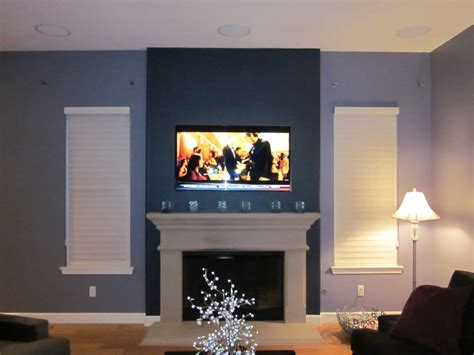 tv mounted above fireplace and in ceiling speakers with