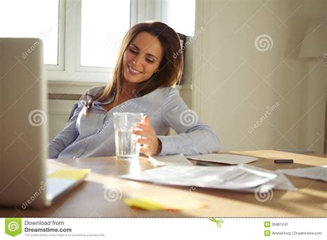 businesswoman sitting at desk in home office stock