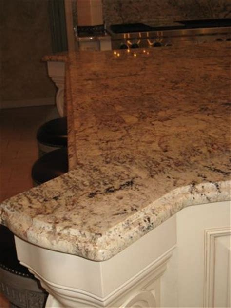 beige kitchen cabinets with typhoon bordeaux granite typhoon bordeaux granite kitchen traditional with curved