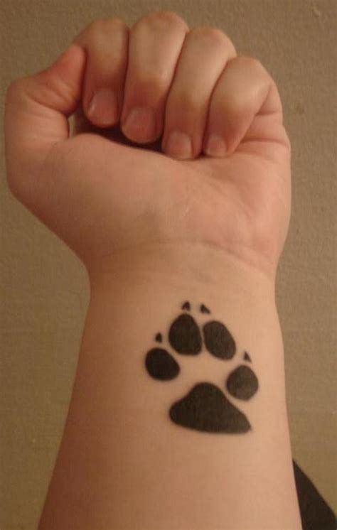 dog paw tattoo on wrist black paw print on wrist