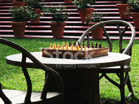 chess table set up table and chairs with chessboard set up outdoors on lawn