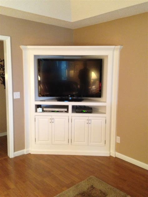 built in white corner media cabinet with shelves of