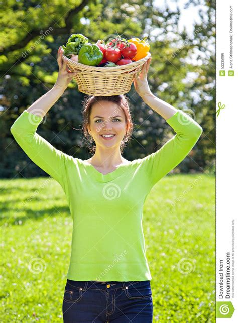 woman with fruit basket on head brunette woman with basket of fruit and vegetables over