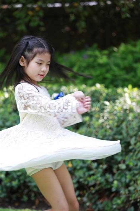 tiny pretender model japanese a cute little asian girl is spinning in joy stock photo