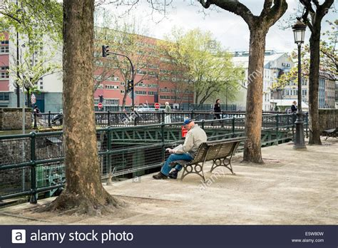 paris park bench man reading on a park bench along the canal st martin in