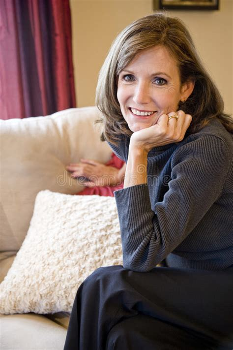 middle aged woman relaxing  living room sofa stock image
