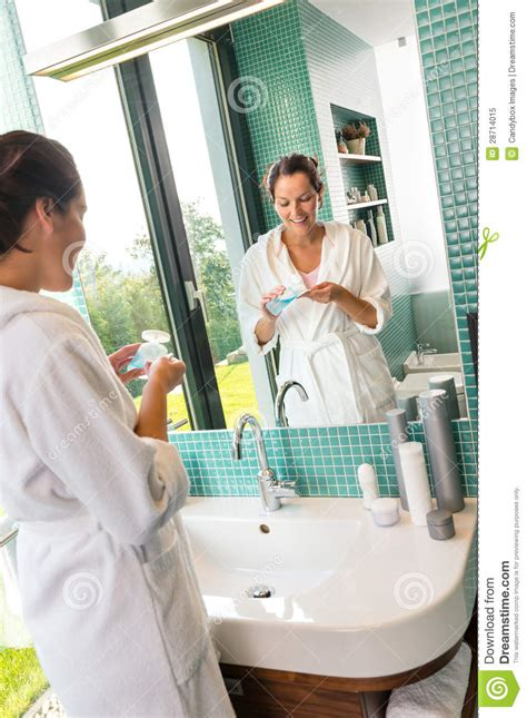 women using the bathroom smiling woman using skin care lotion bathroom royalty free