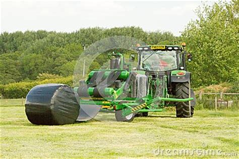 modern john deere green tractor with round bale wrapper