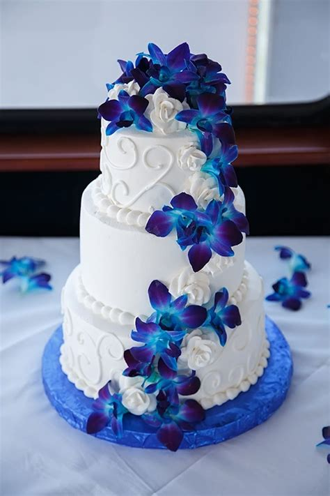white wedding cake with swirls and blue orchid