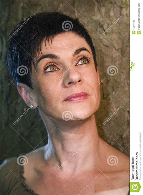 middle age women with blue hair beautiful woman by the tree looking up stock photo image