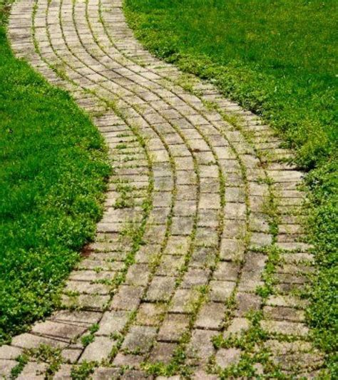 backyard walking paths a brick walking path that curves with grass stock photo