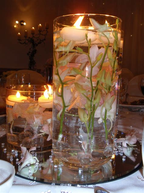 wedding reception flower centerpieces bowl filled with pink lotus and floating candles for