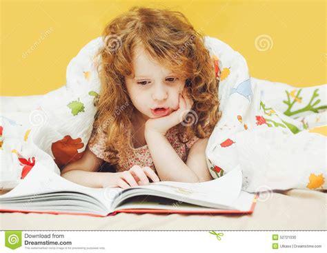 fille lisant un livre dans le lit avant d aller