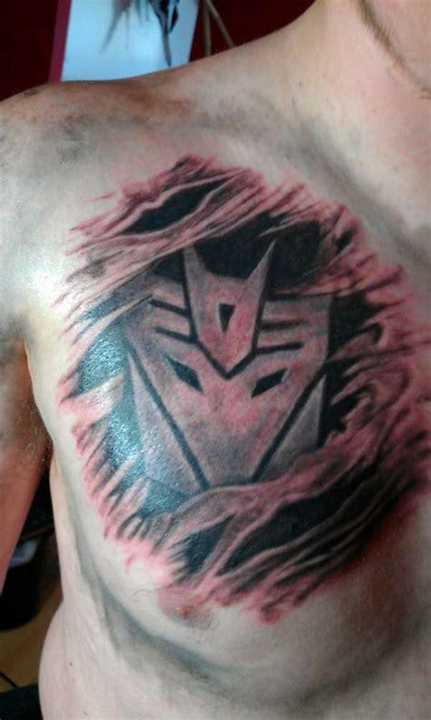 logo tattoo man ripped skin transformer logo tattoo on man right chest