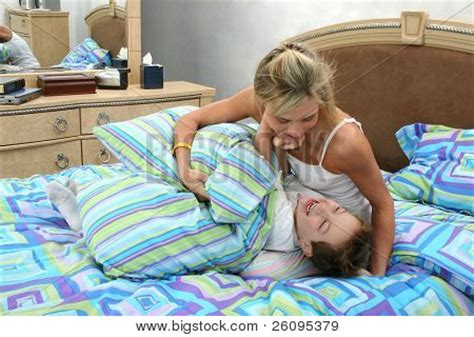 mom son bed mom and son having tickle fight at home in bed stock