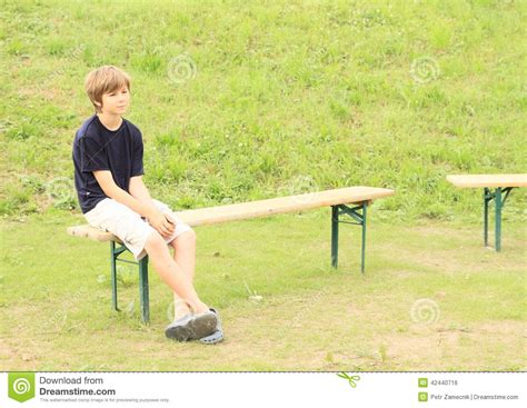 sitting on a bench boy sitting on bench stock photo image 42440716