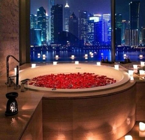 romance in the bathroom bathtub full of rose peddles and candles romantic