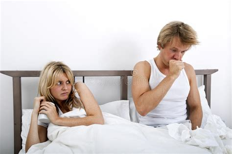 coughing in bedroom only scared woman looking at man coughing in bed stock