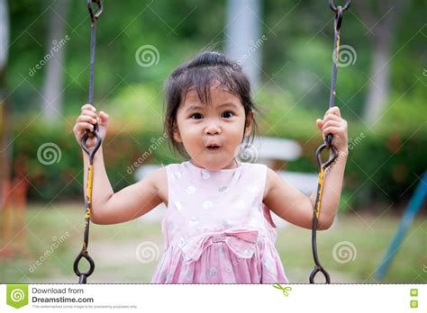 swing asia surprised face of asian cute little girl while she playing