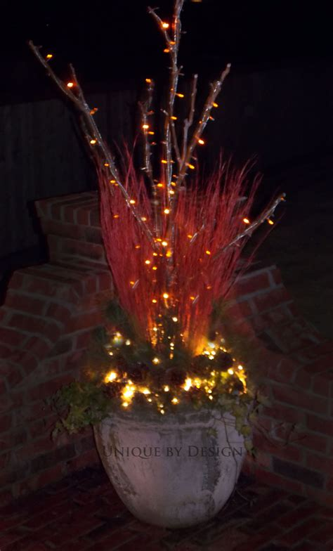 lighted tree in urn lighted outdoor urn with ornamental grasses and greenery