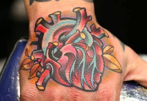 tattoo new school hand new school heart hand tattoo by guru tattoo