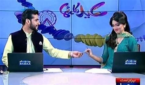 male newscaster giving eidi to female newscaster during