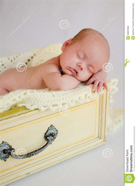 Baby In Drawer by Newborn Baby Sleeping In Yellow Drawer Stock Images