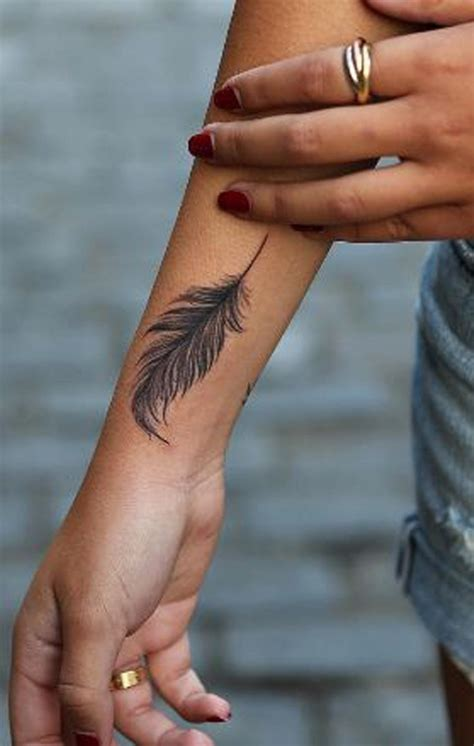 feather tattoo on girl s arm 20 feather tattoo ideas for women feather tattoos