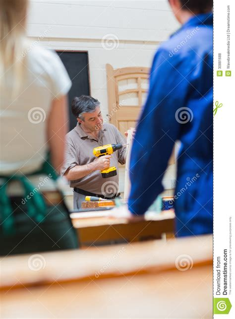 teaching woodworking of a woodworking class explaining royalty free