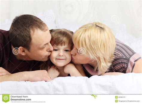 kissing on the bed happy father and mother lie on bed and kiss little stock image image 32395721