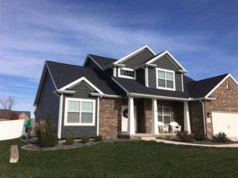 dark grey siding  white trim  dark roof brown