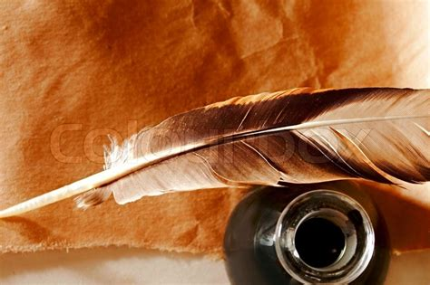 Fn A Quill feather and ink bottle on paper background stock photo colourbox