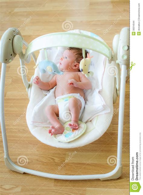 baby boy swing cute newborn baby boy sitting in electrical swing stock
